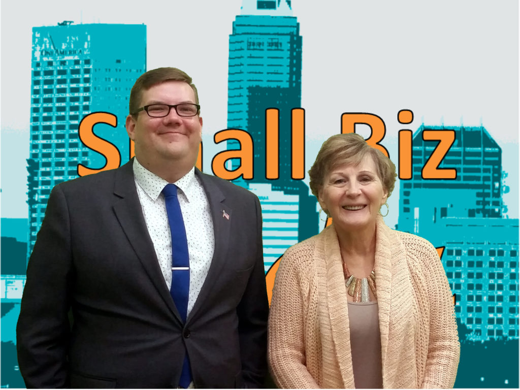 Ryan Henry and Terri L. Moore in front of the Small Biz Indy logo( orange text over an aqua colored skyscape of Indianapolis)