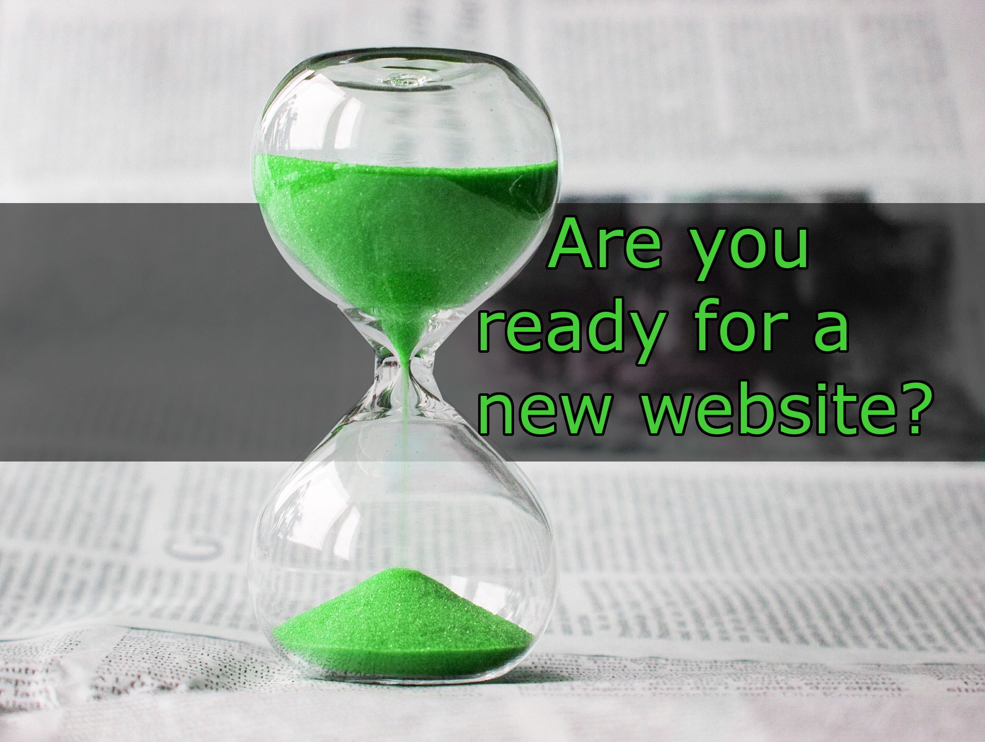 "The text ""Are you ready for a new website?"" , in green text, over a faded black bar, next to a glass hourglass with green sand, over a newsprint background."