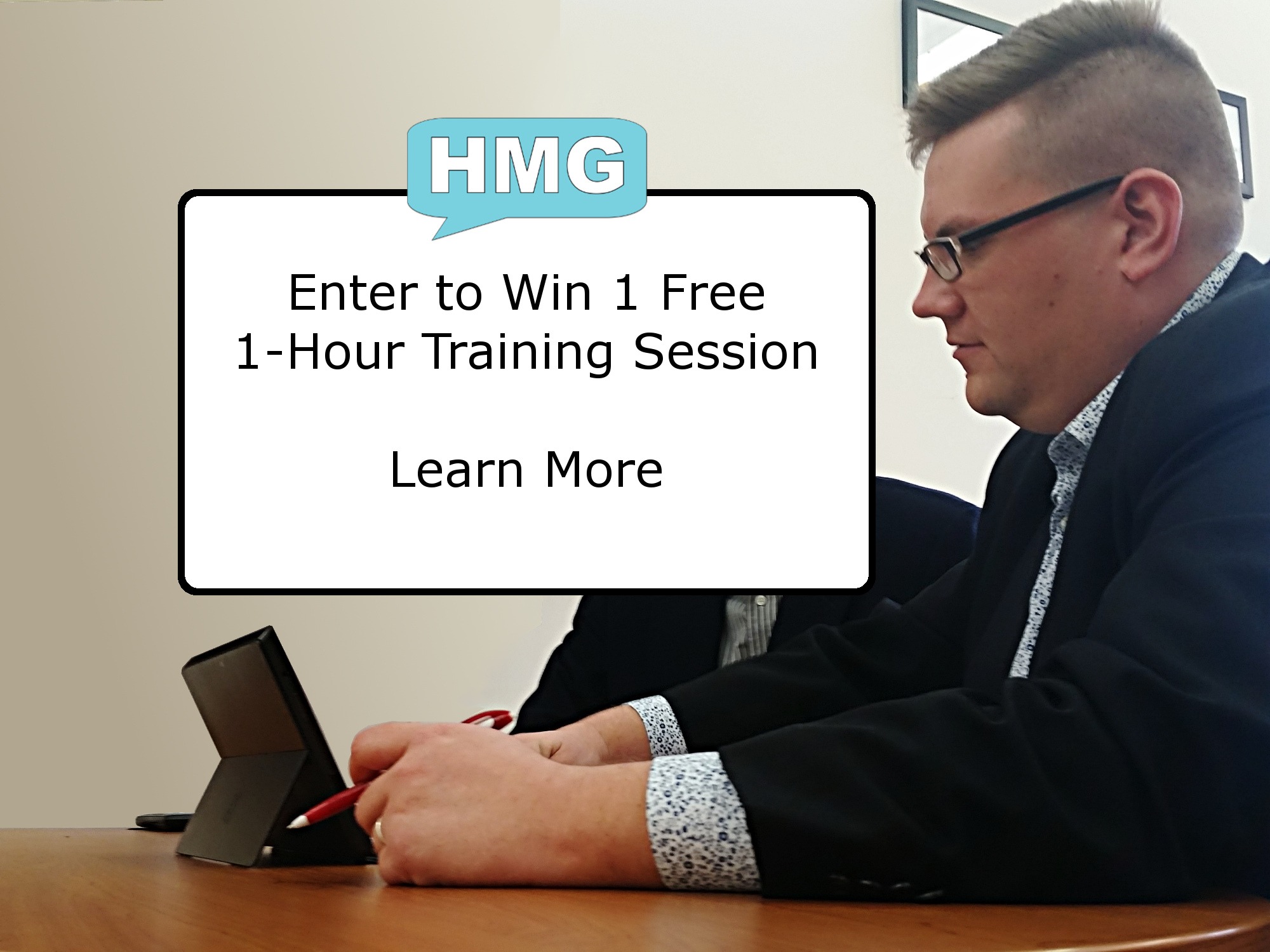 "An image of Ryan Henry working with a client, overlayed with a white box, surrounded by a black outline, with the text ""Enter to Win 1 Free 1-Hour Training Session - Learn More"". Over the white box, is the Henry Marketing Group logo which is a teal chat box with the letters ""HMG"" in white, inside the chat box."