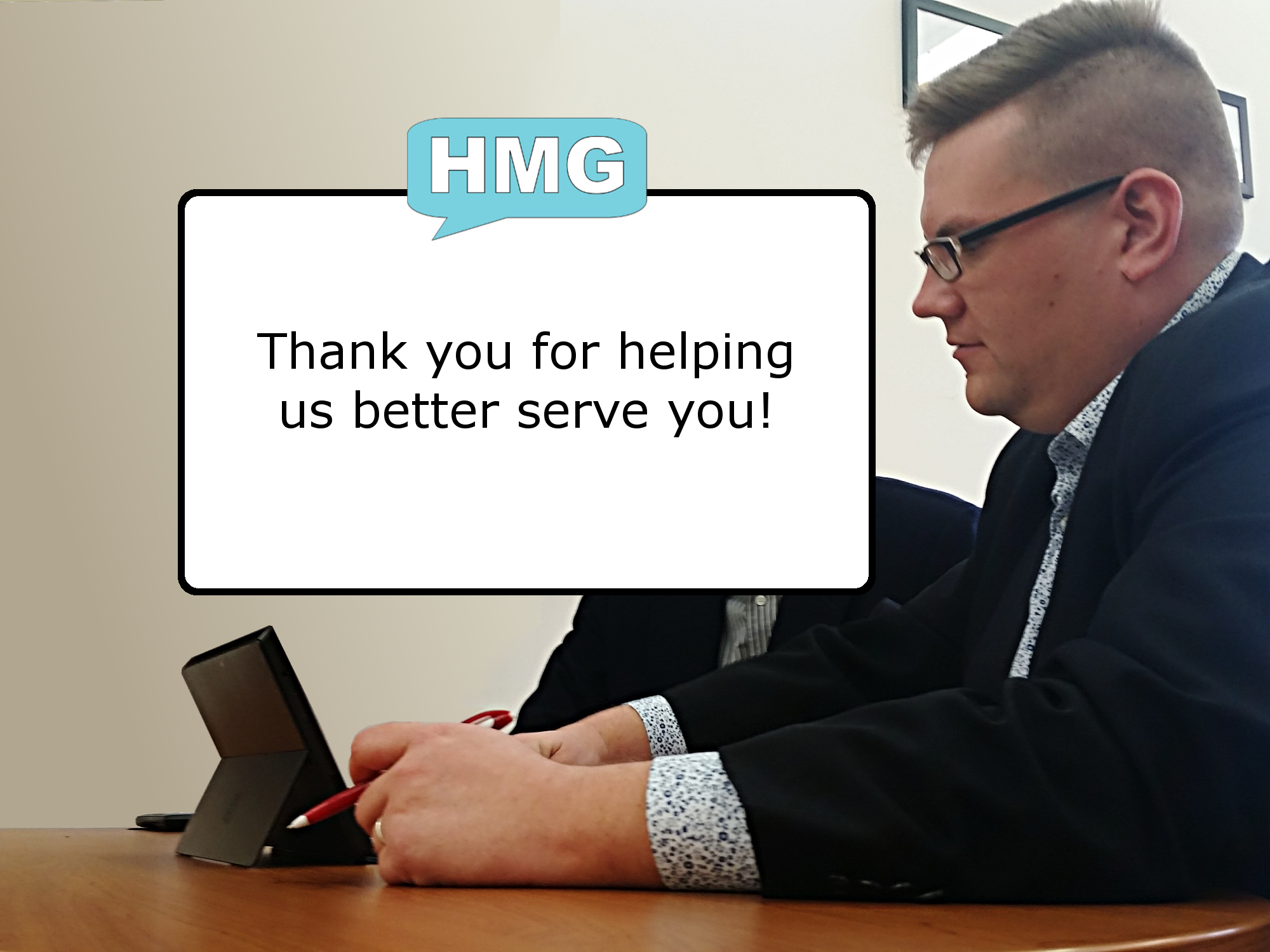 "An image of Ryan Henry working with a client, overlayed with a white box, surrounded by a black outline, with the text ""Thank you for helping us better serve you!"". Over the white box, is the Henry Marketing Group logo which is a teal chat box with the letters ""HMG"" in white, inside the chat box."